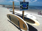 These SUP racks were displayed at the 2012 Waterman's Challenge on Cocoa Beach, Florida. The SUP rack in the foreground is a single board display rack with paddle holder.